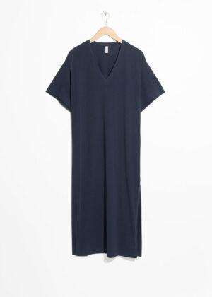 Knälång v-ringad klänning med v-ringning. Klänningen är blå och romantisk.