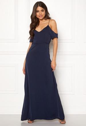 Lång långklänning med axelband. Klänningen är blå och modemedveten.