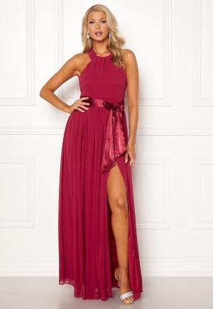 Lång långklänning med axelband. Klänningen är röd och flirtig.