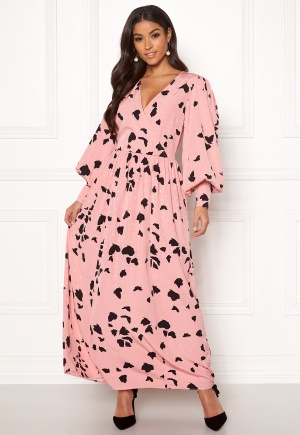 Lång maxiklänning med v-ringning. Klänningen är rosa och elegant.