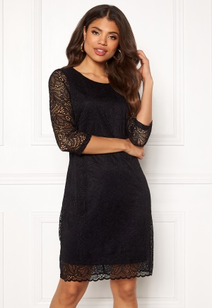 Kort spetsklänning. Klänningen är svart och modemedveten.
