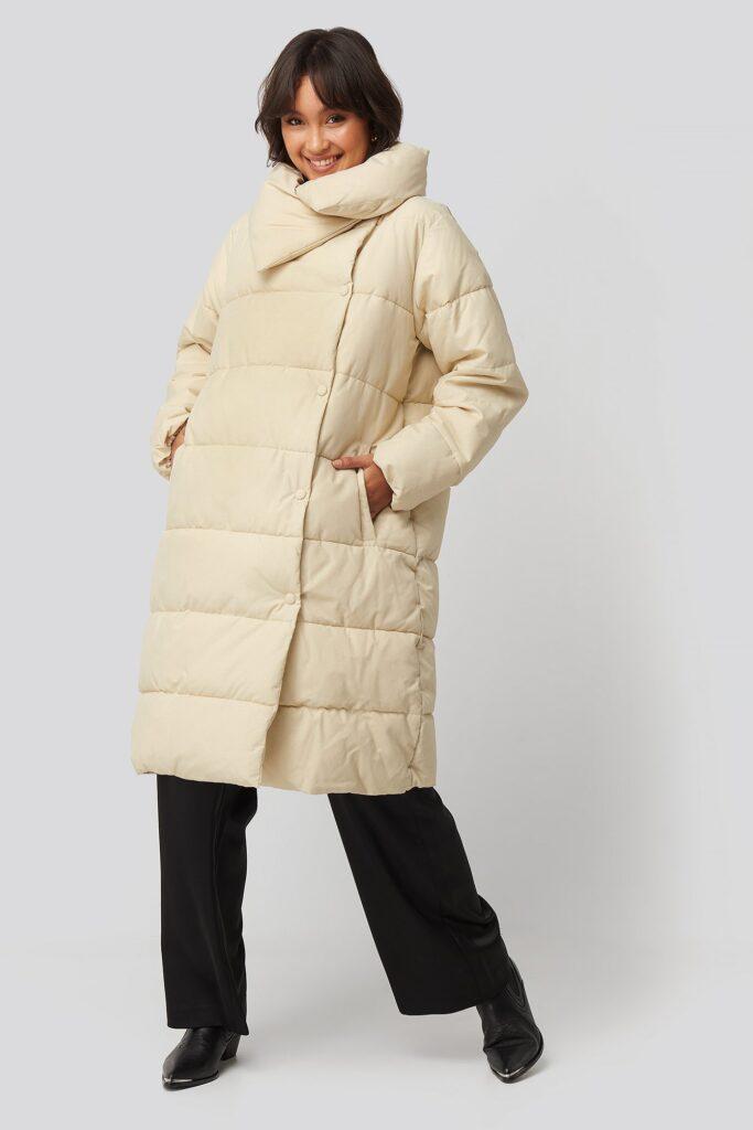Pösig beige vinterparka med stor hög krage.