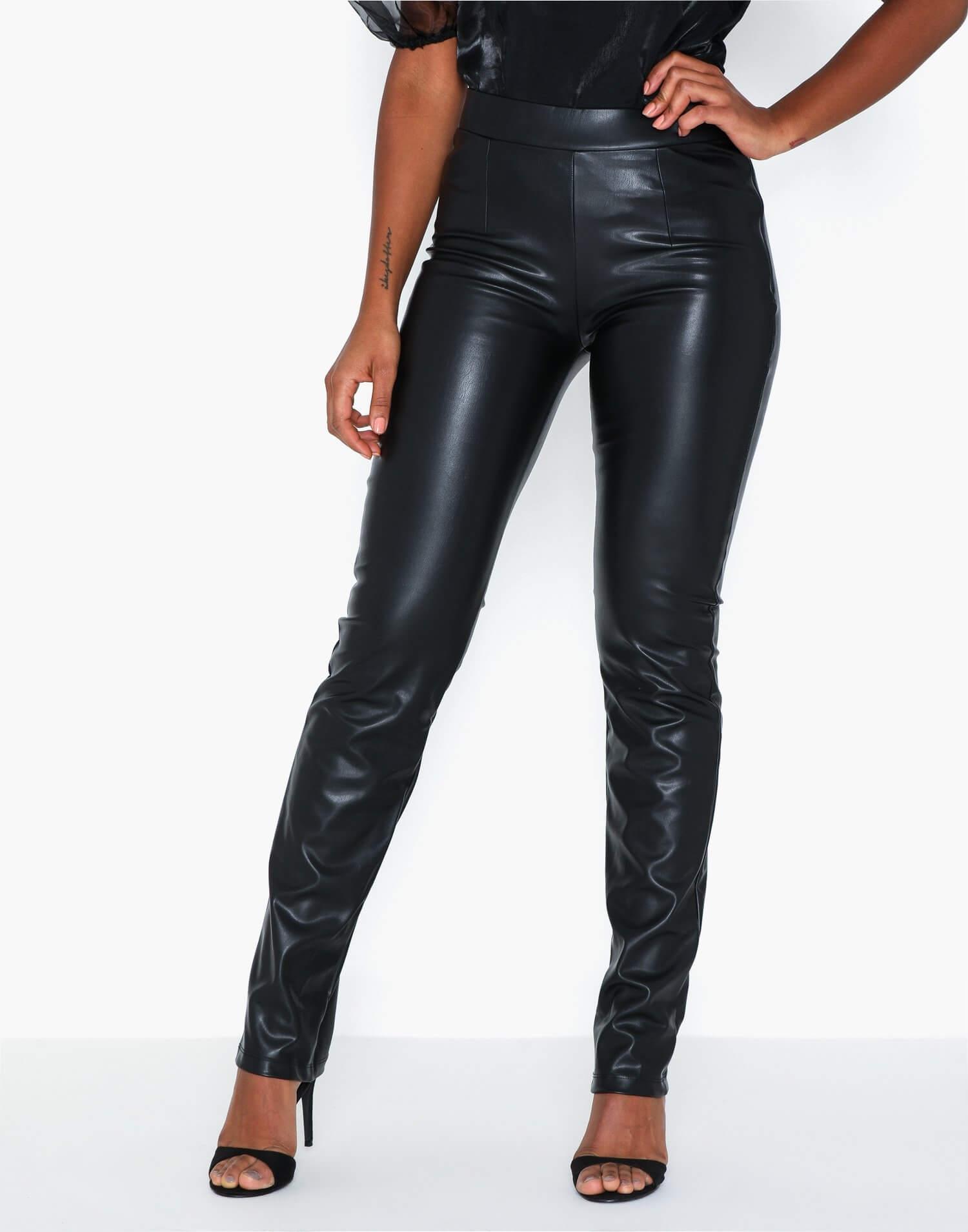 Svarta skinnbyxor från Nelly i glansig läderimitation. Stretchig tight byxlinning och lösare nedtill.