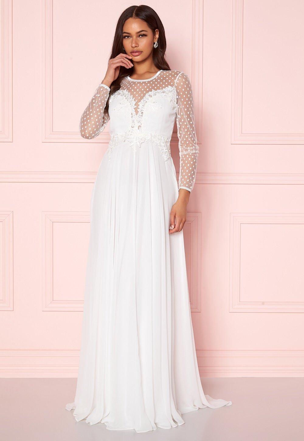 Vit bröllopsklänning med spets och långa ärmar.