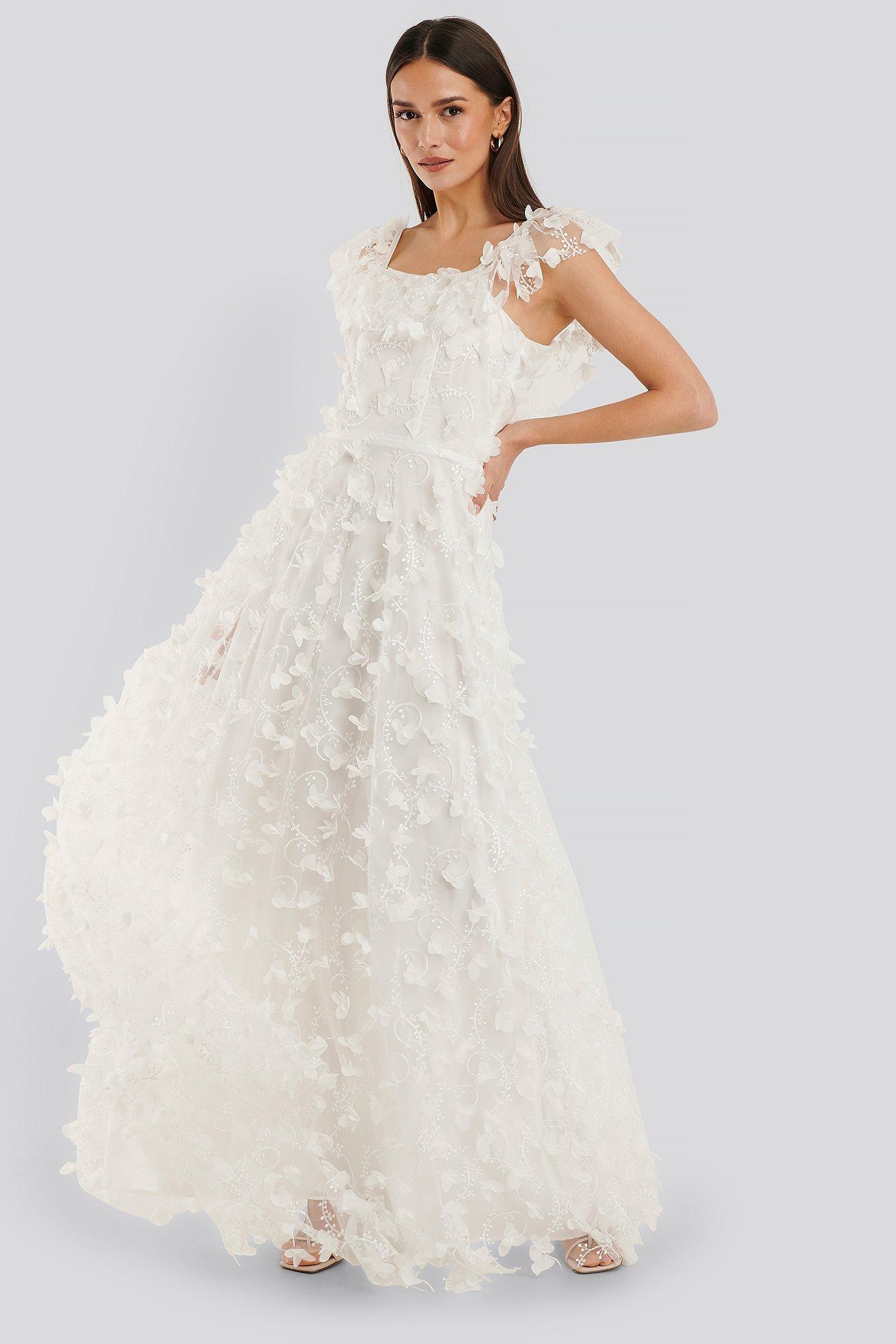 Vit bröllopsklänning i spets med korta ärmar.