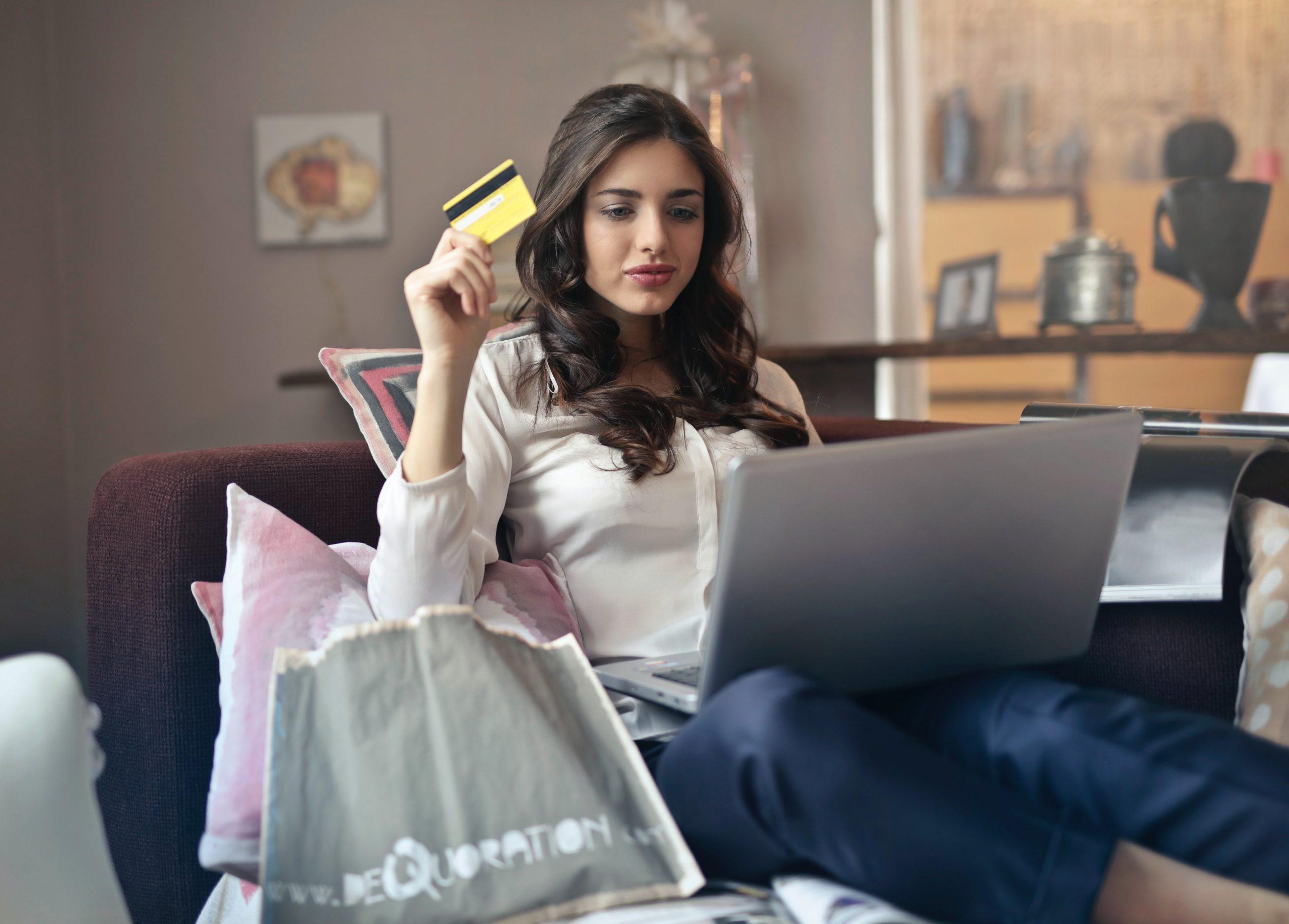 Kvinna sitter framför dator och hållar bankkort i handen