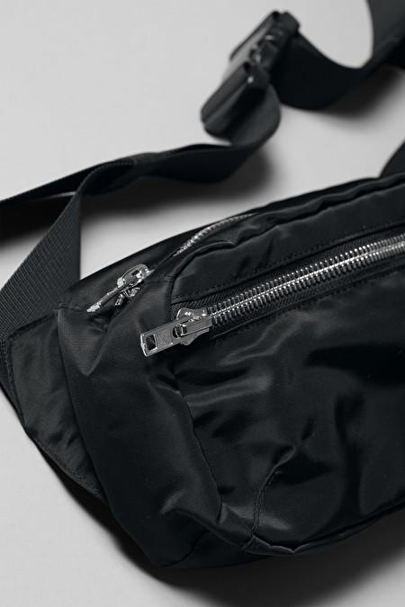 Svart magväska med ett fack. Silverfärgad dragkedja och justerbar rem.