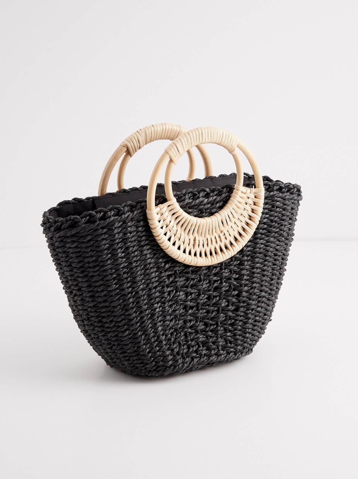 Liten väska i svart och vitt stråmaterial med runt handtag