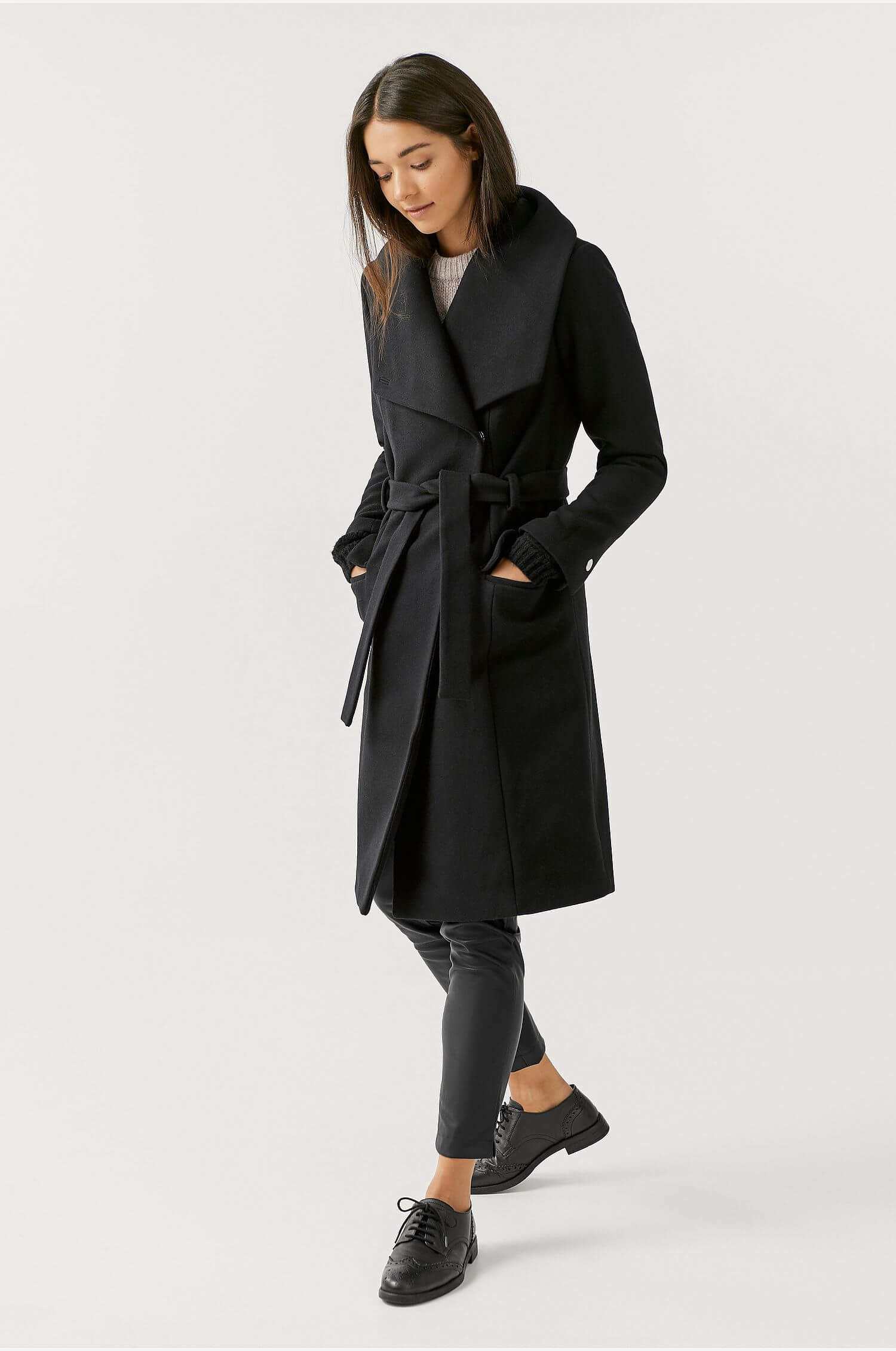 En svart knälång kappa med knytskärp från Ellos Collection.