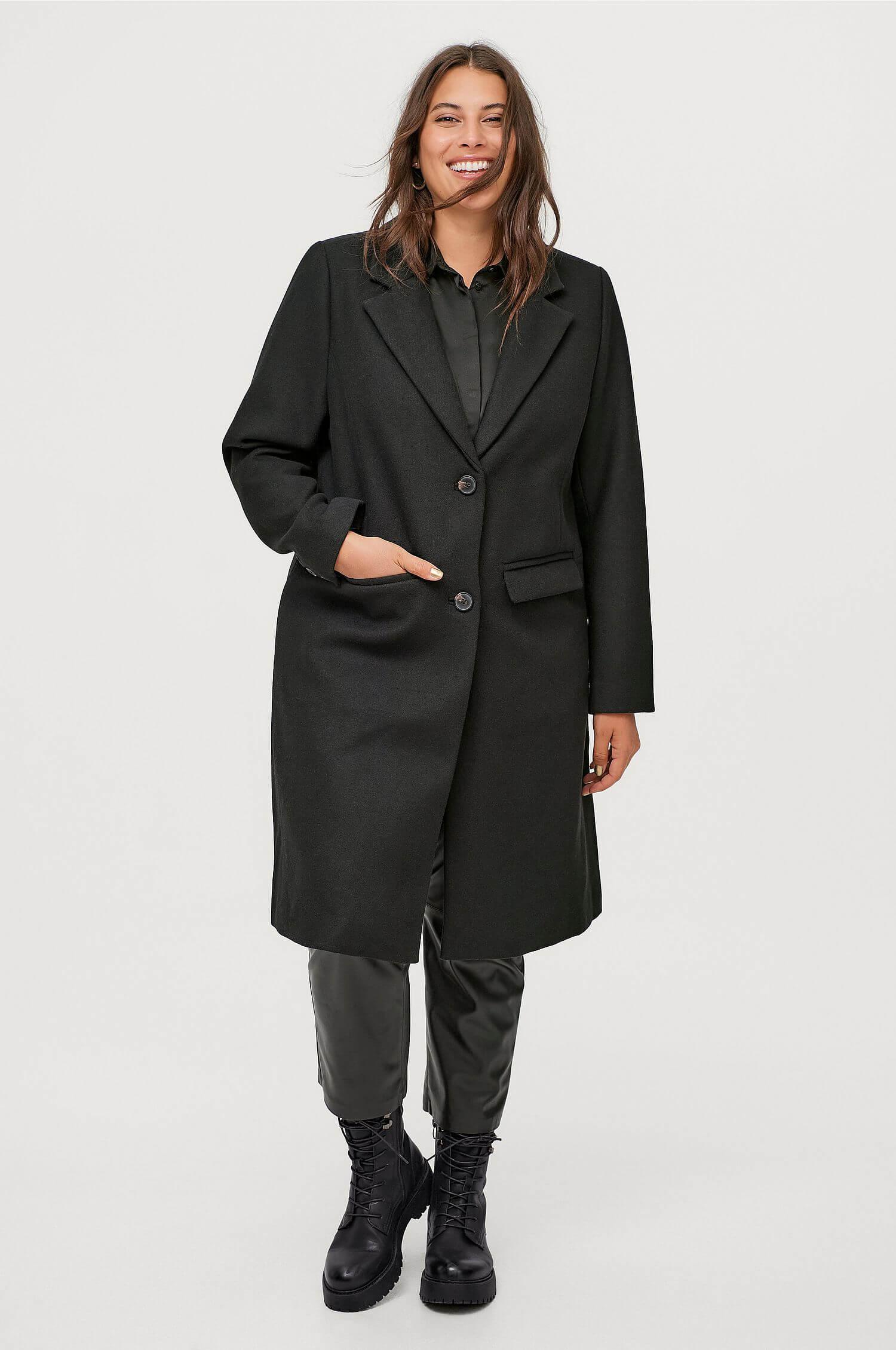 En svart ullkappa i plus size-modell från Ellos Plus Collection.