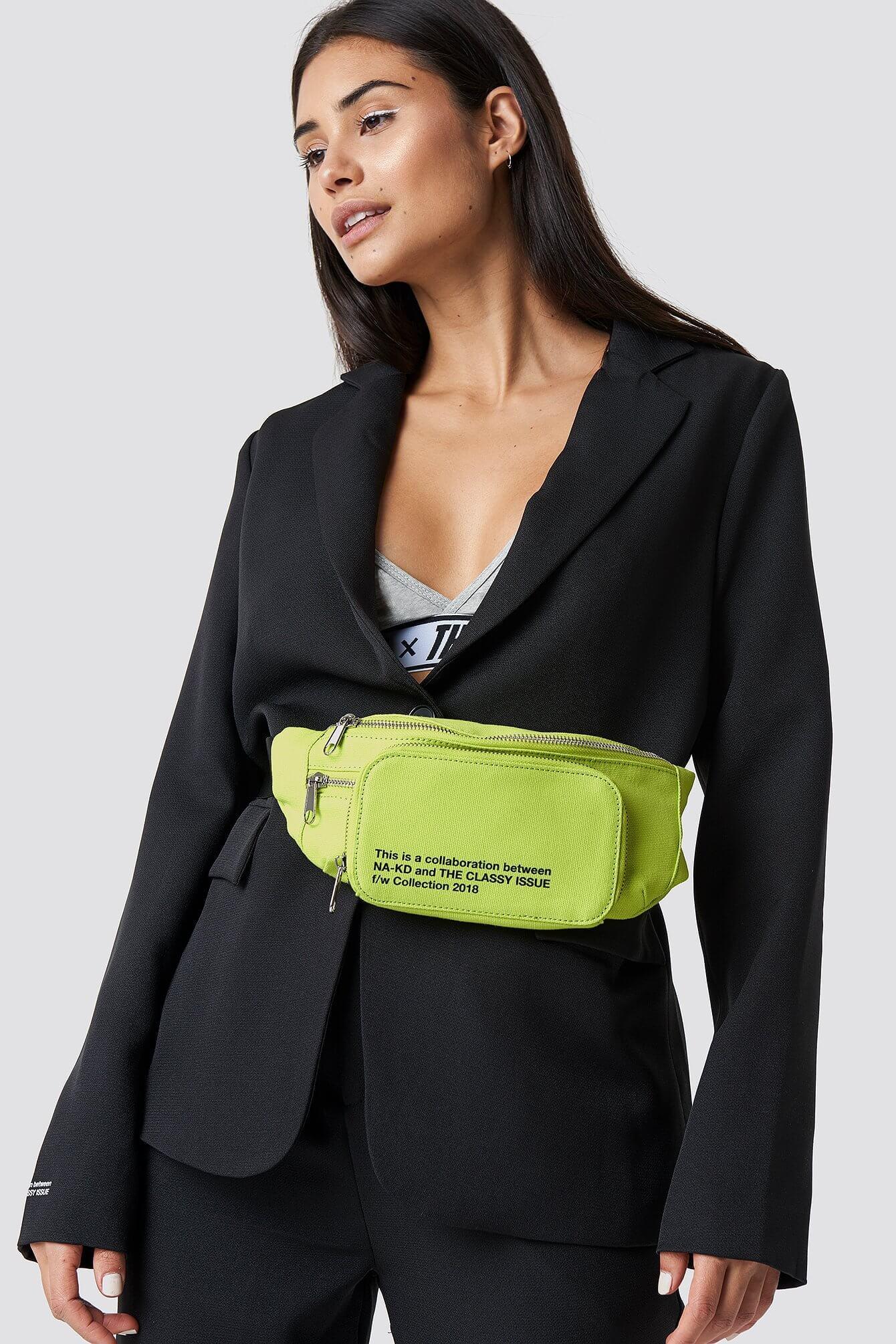 Magväska i färglad gul nyans med tillhörande rem och spänne. Två fack med dragkedja.