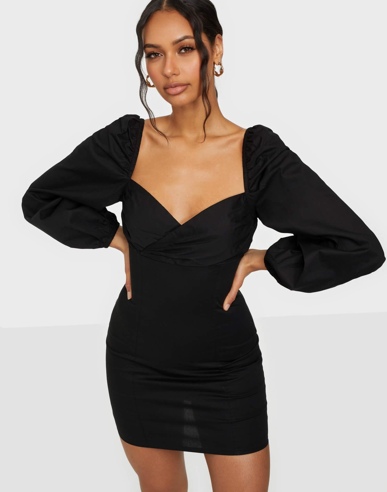 en taight svart klänning med puffiga länga ärmar