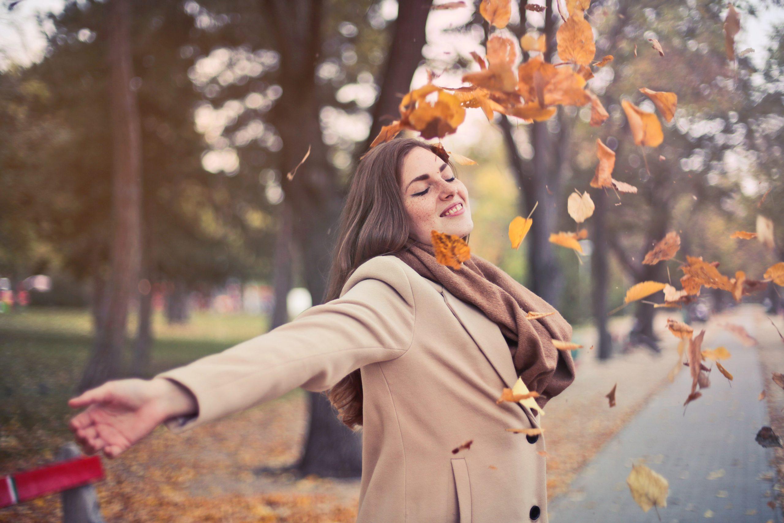 Kvinna utomhus sträcker ut armarna i höstlöv. Har en beige kappa på sig. Höstig miljö.