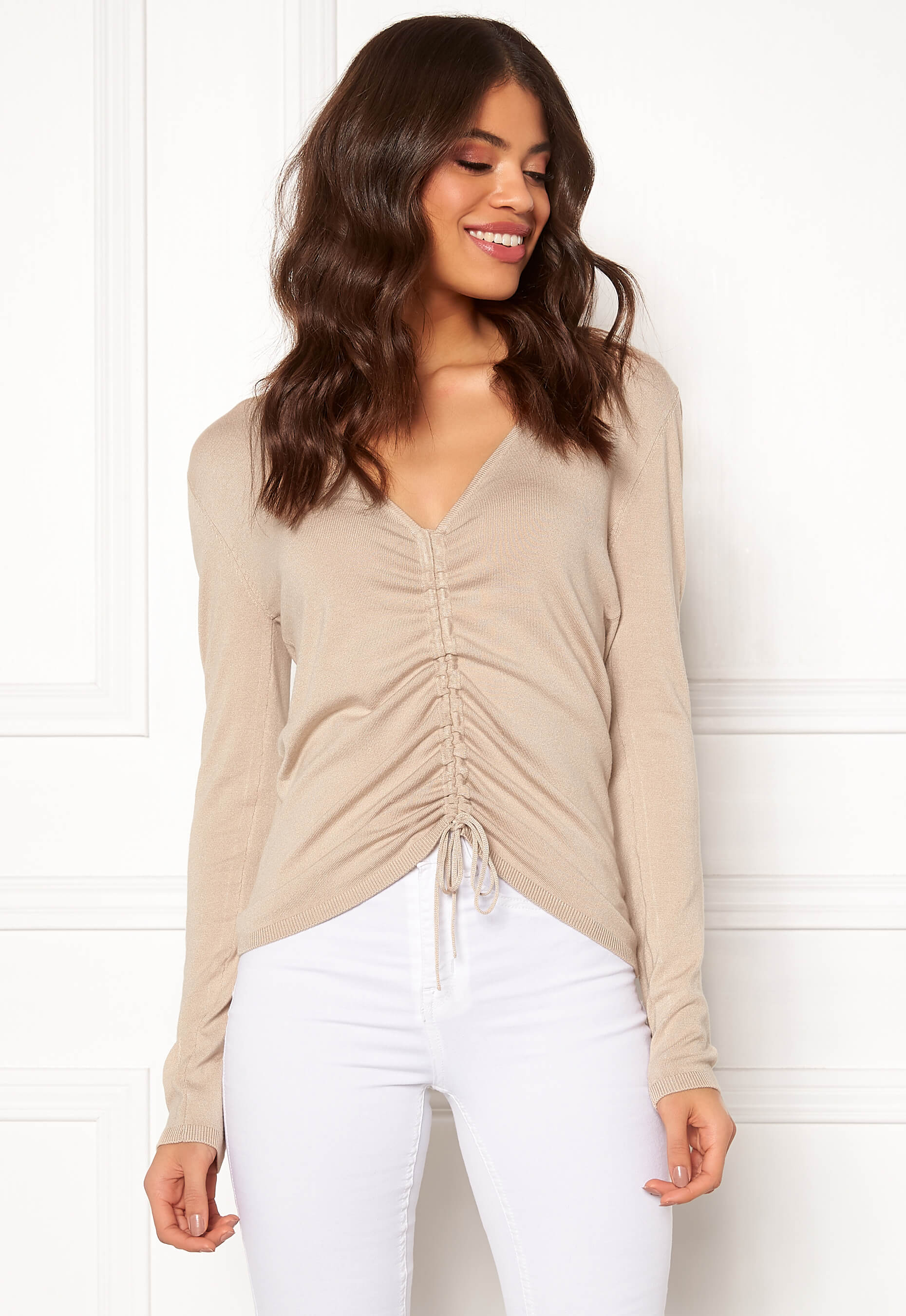 Beige långärmad tröja med dragsnöre i mitten. Finstickat material.