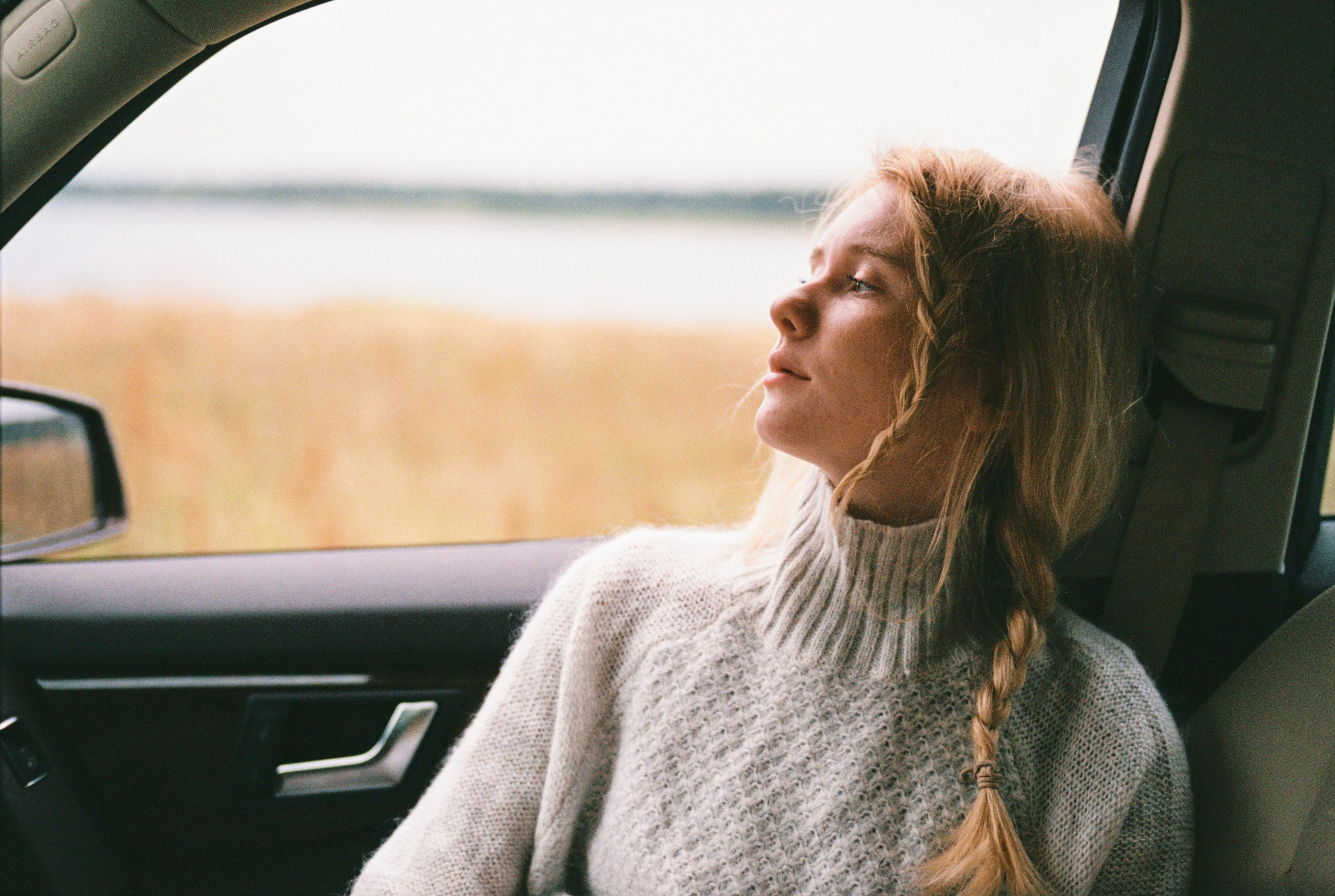 Kvinna sitter i bil och tittar ut genom fönster. Hon bär en grå stickad polotröja.