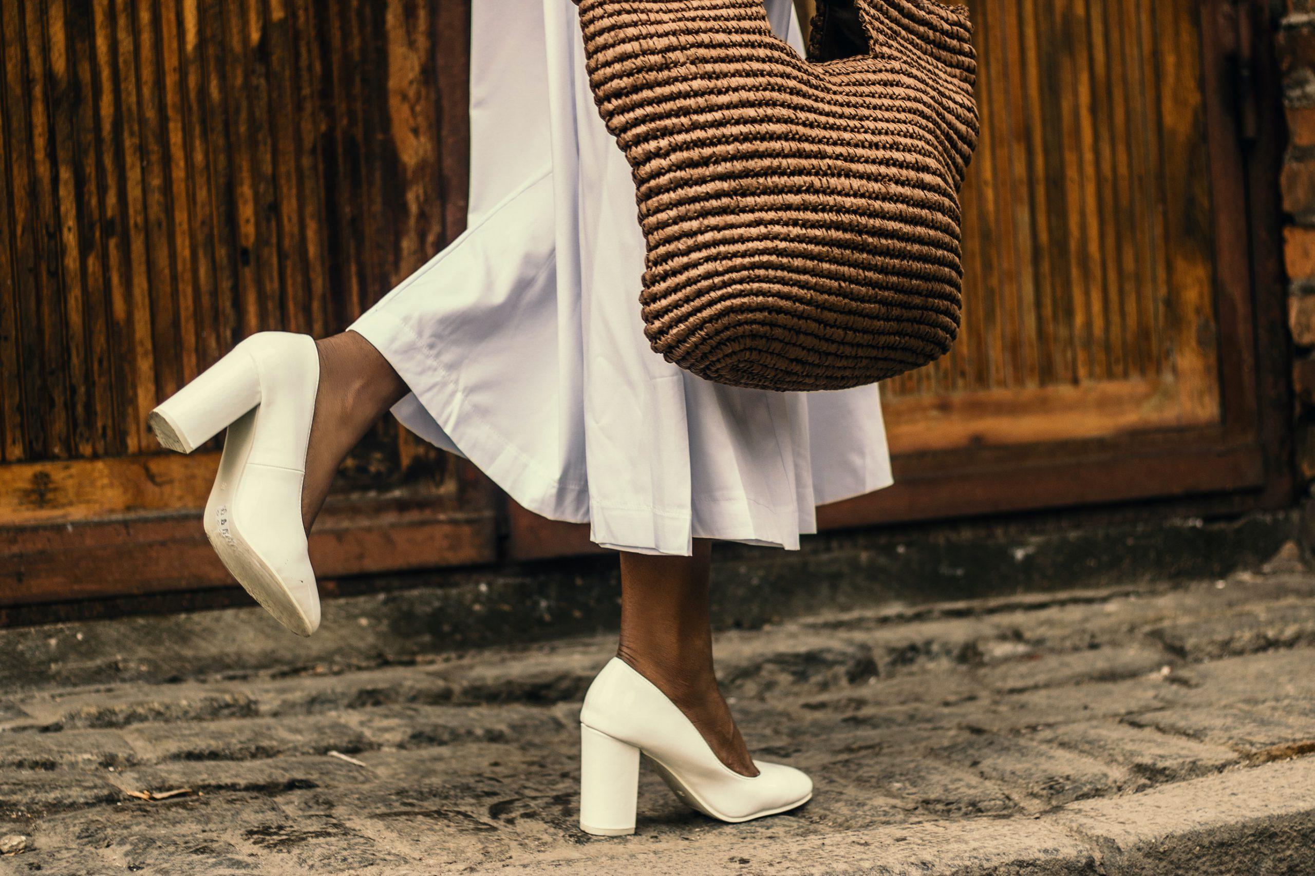 kvinna med vit vadlång kjol och stråväska