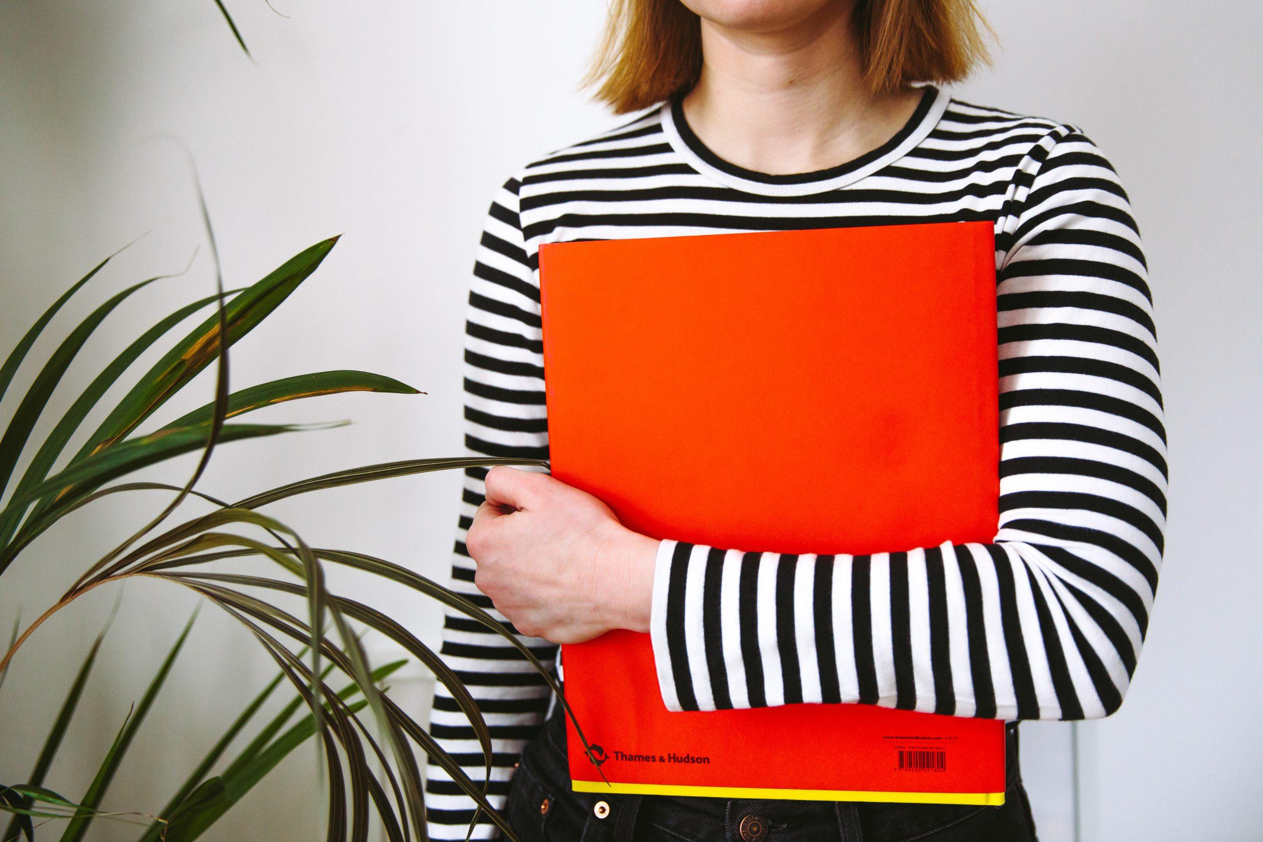 kvinna med randig tröja håller röd pärm
