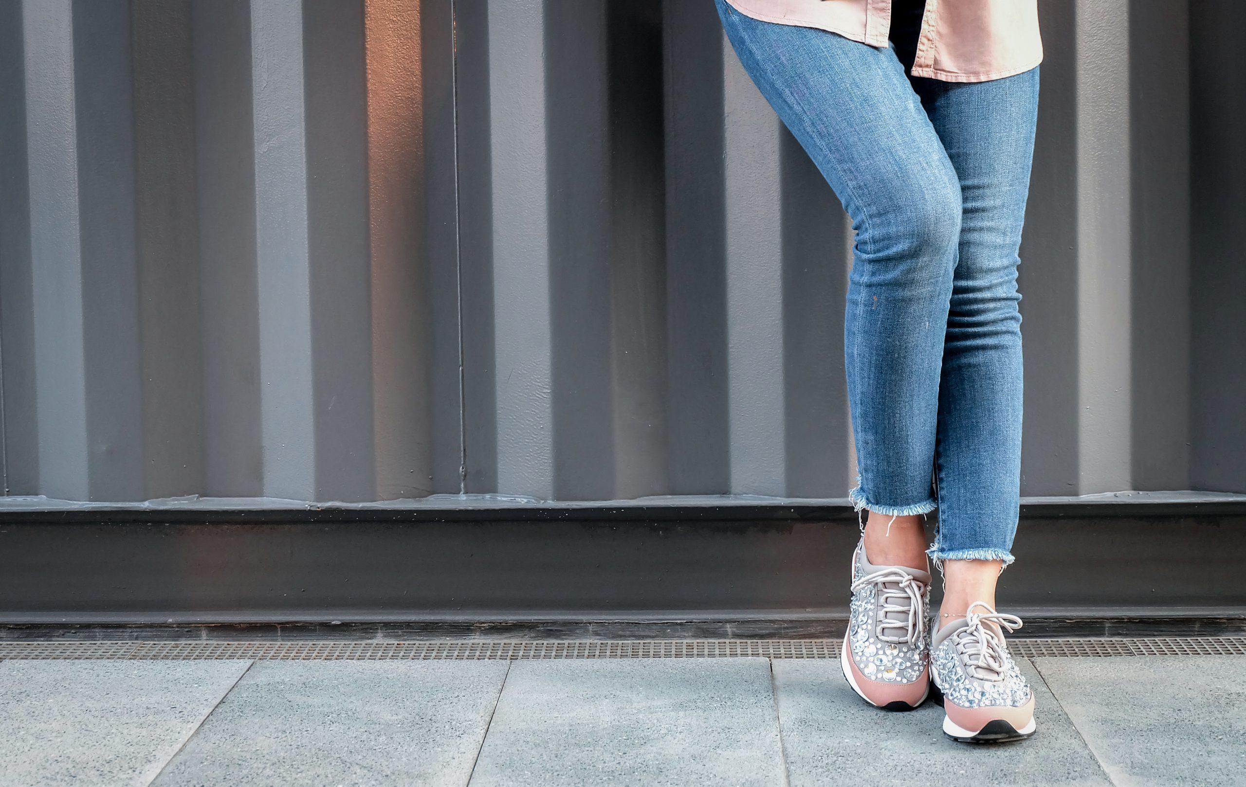 kvinnliga ben med korta jeans och gympaskor