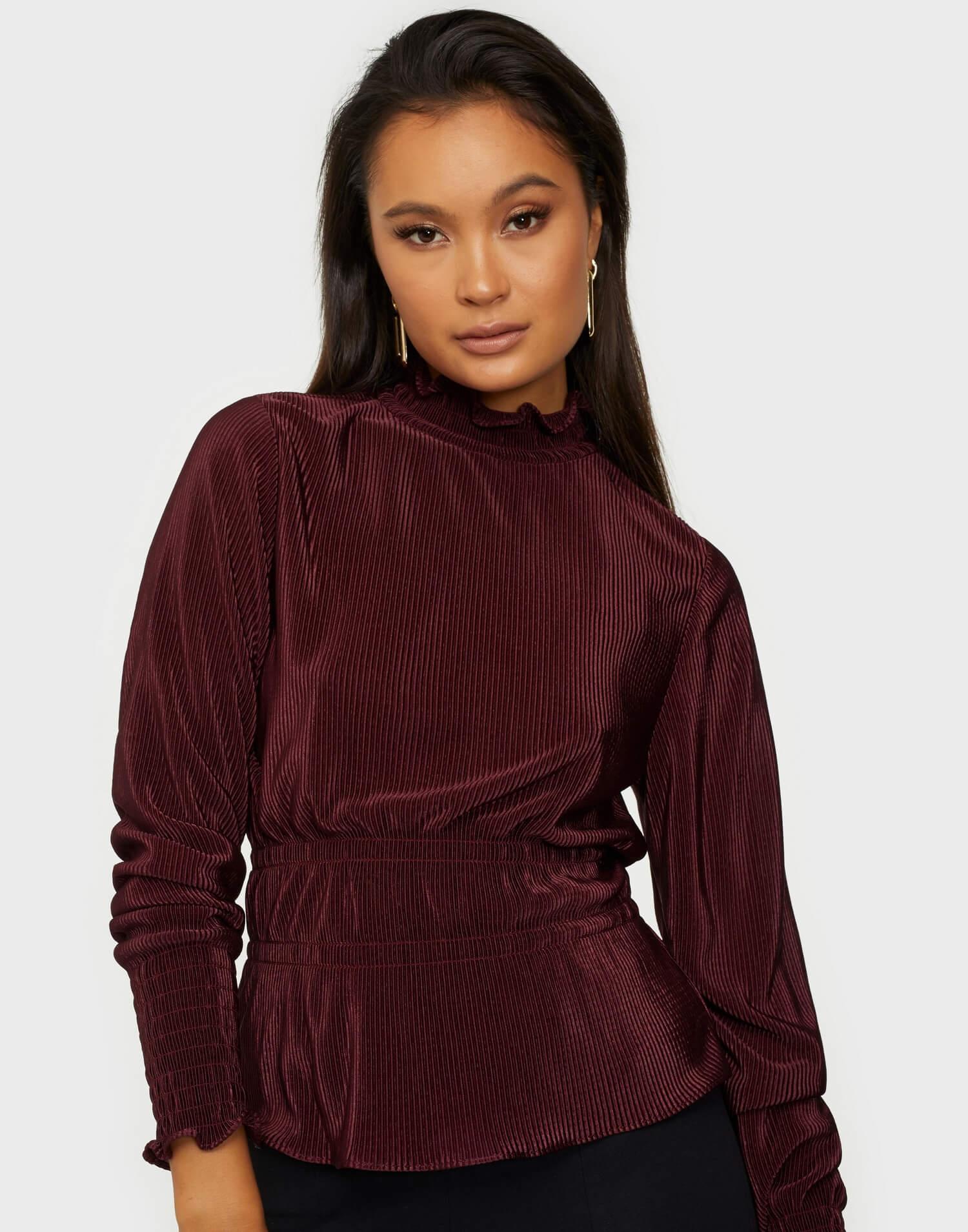 En mörkröd plisserad blus från NLY Trend.