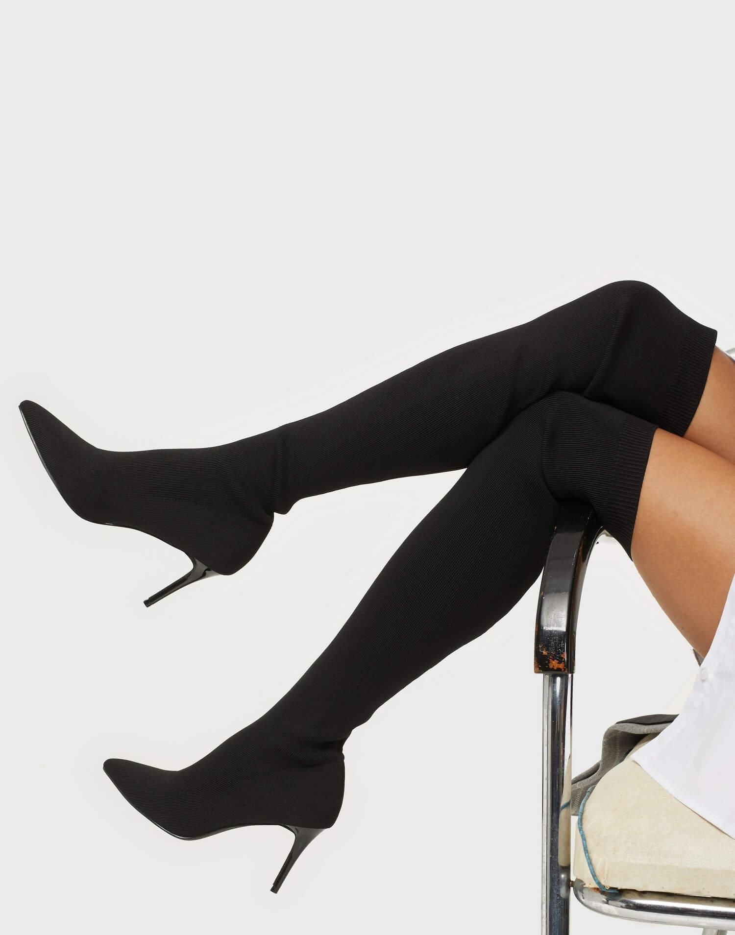Ett par svarta, högklackade skor i over knee-modell från NLY Shoes.