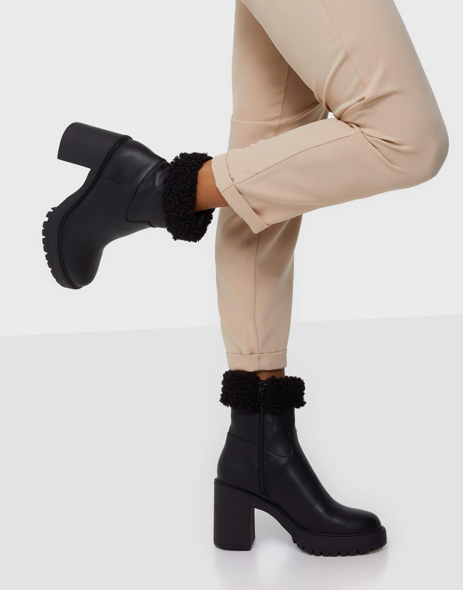 Ett par svarta högklackade stövletter med fuskpälskant upptill, från NLY Shoes.