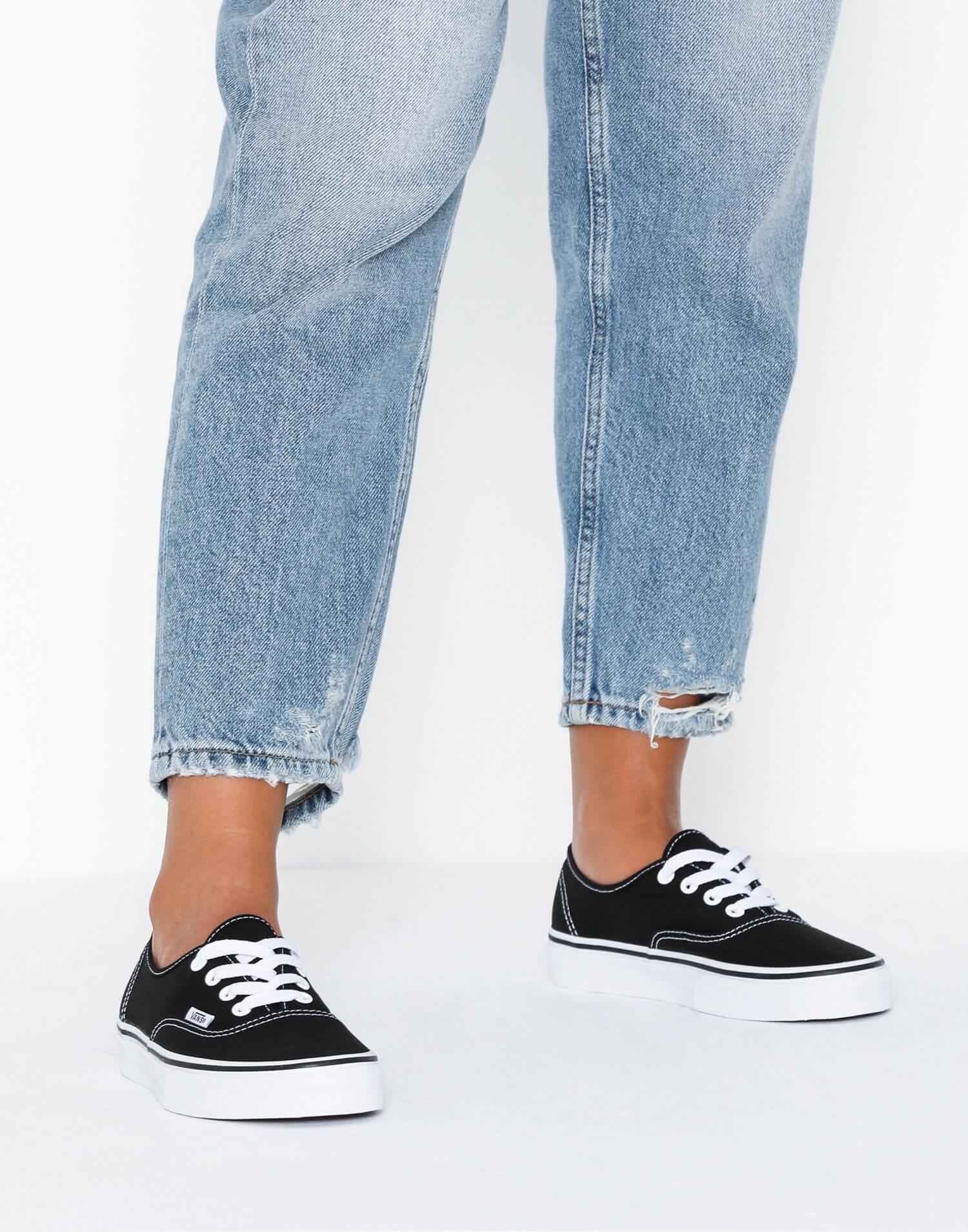 Ett par låga, svarta sneakers från Vans.
