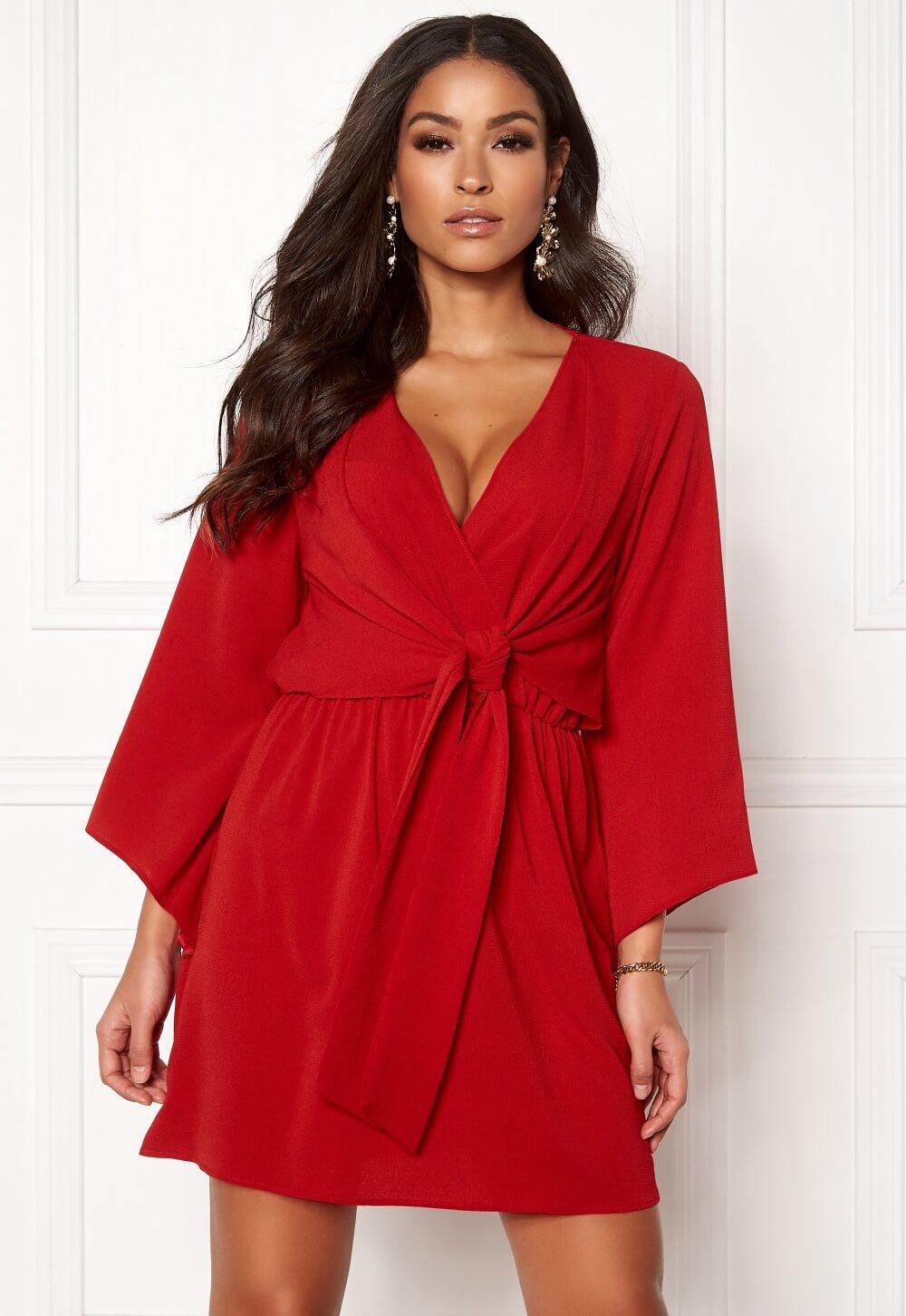 En röd klänning med knytdetalj i midjan.