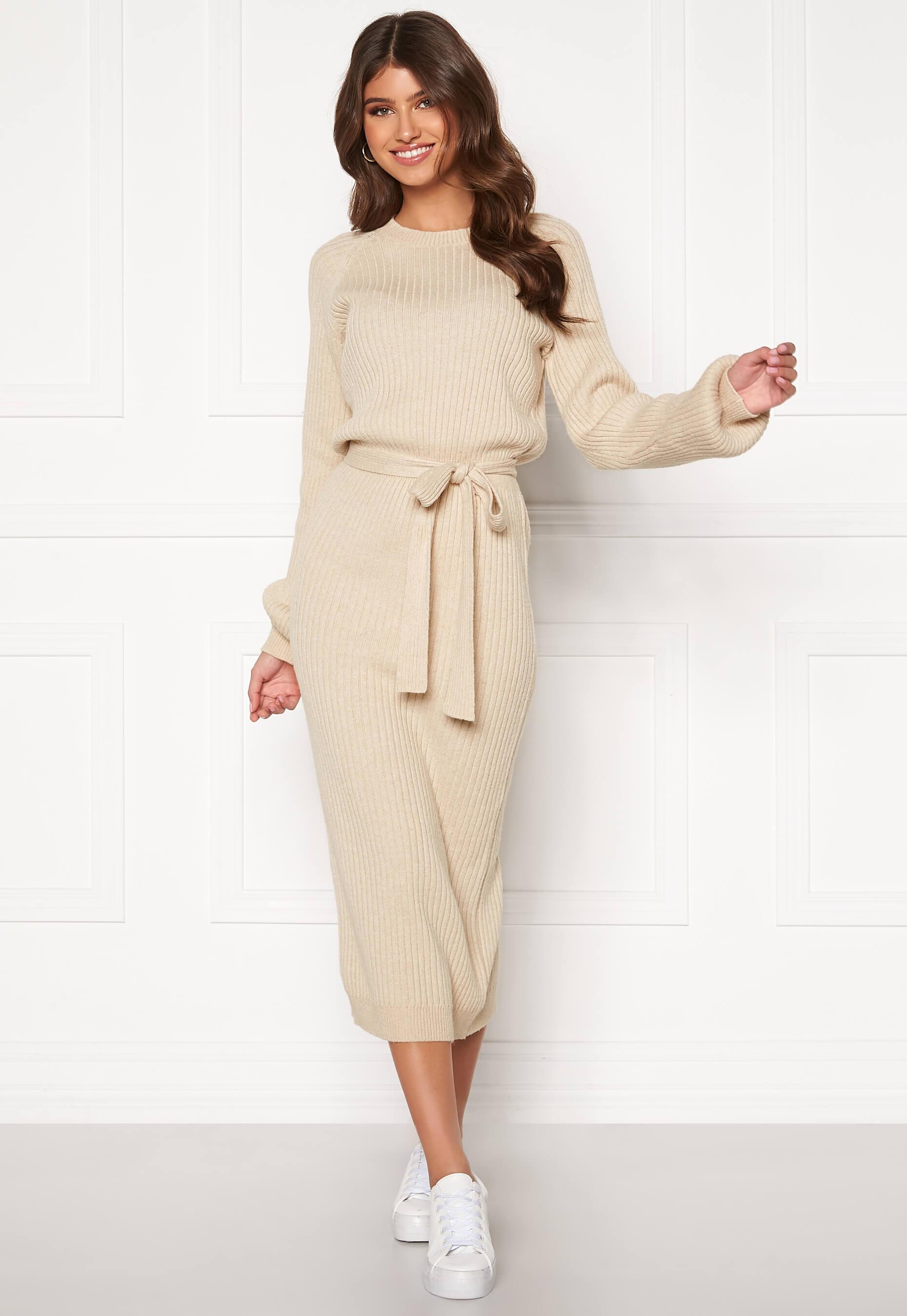 Lång beige ribbstickad klänning med knytband i midjan.