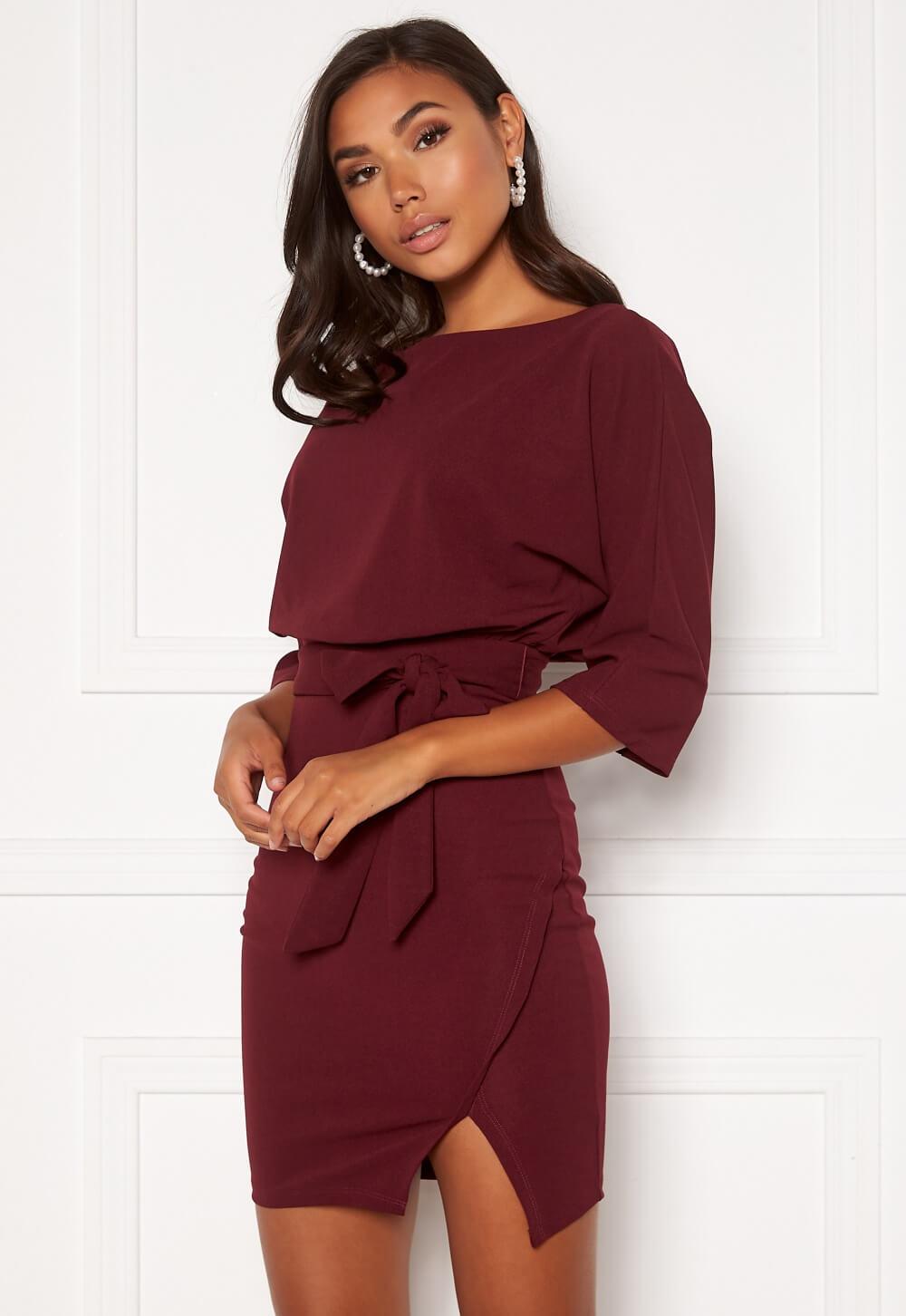 Vinröd klänning med lös överdel och tightare underdel.