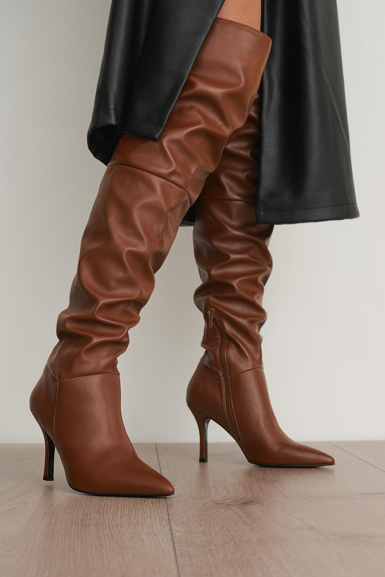 Ett par bruna, högklackade skor i over knee-längd.