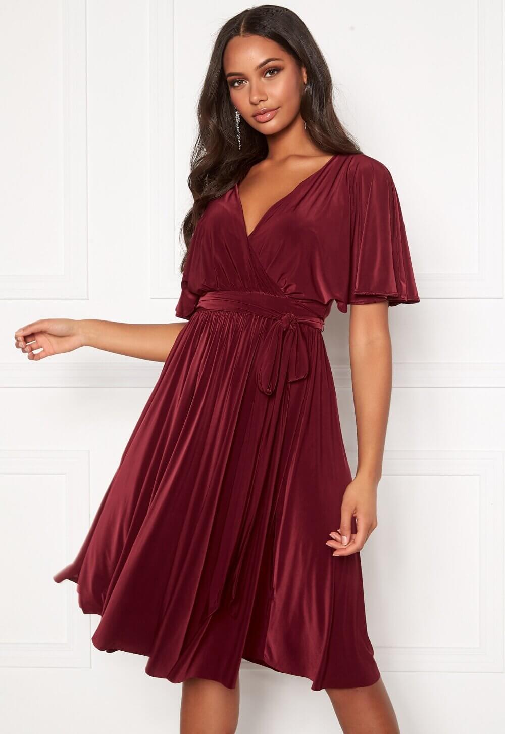 En knälång röd omlottklänning.