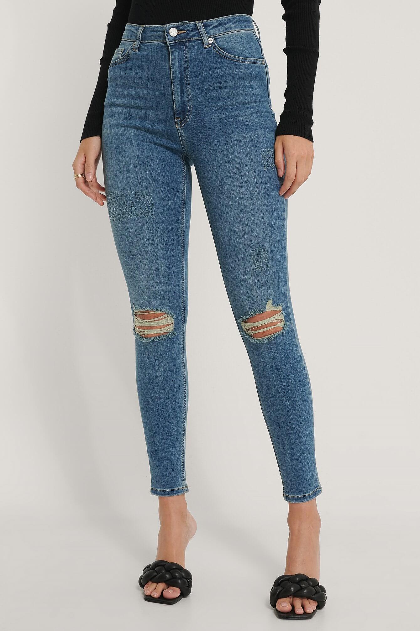 Ett par high waisted skinny jeans med hål på knäna, från NA-KD.