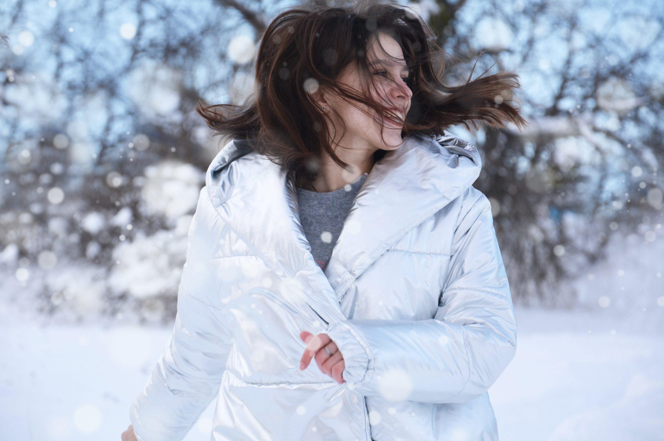 springande kvinna i varm vinterjacka