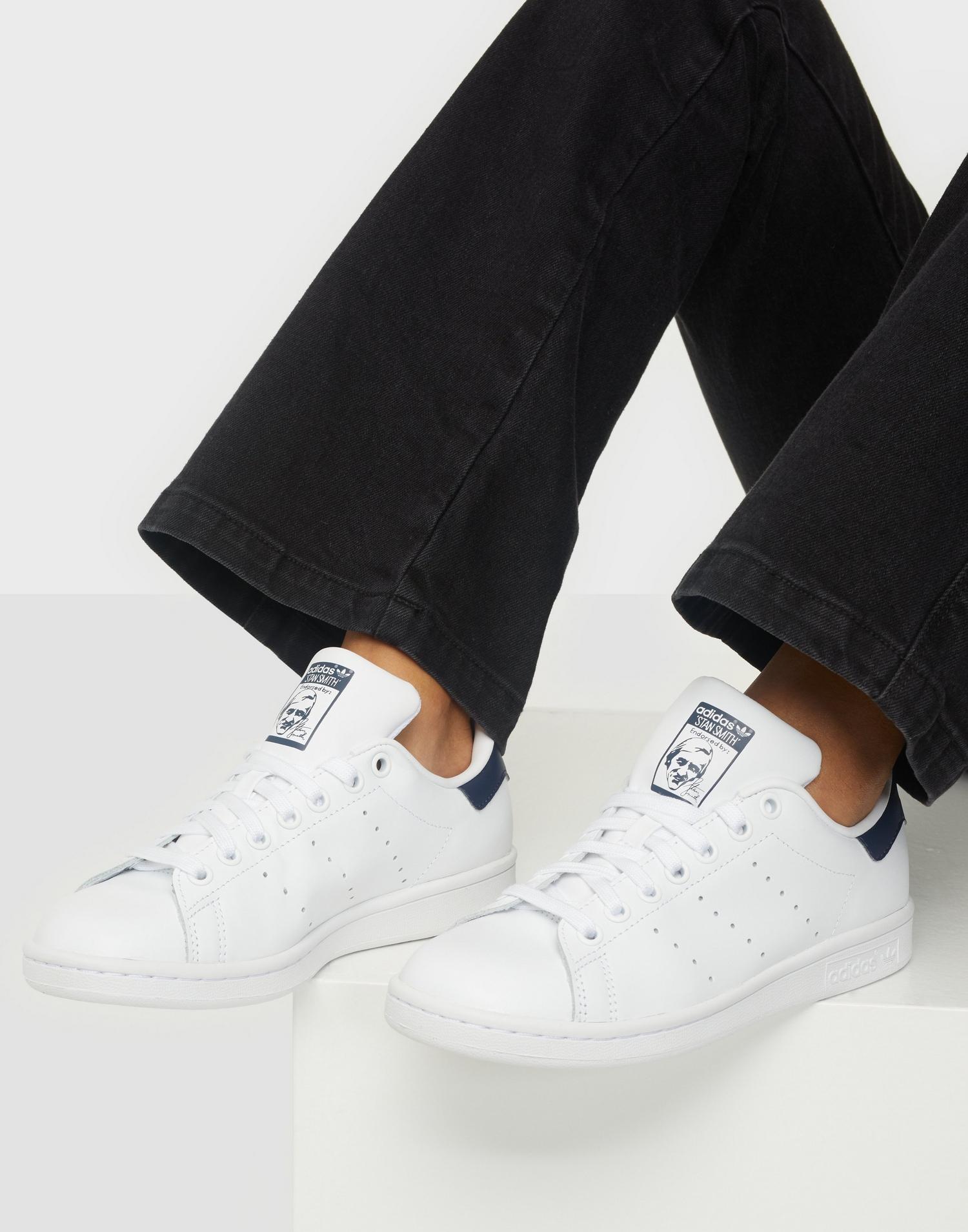 Ett par sneakers i vit textil från Adidas Originals.