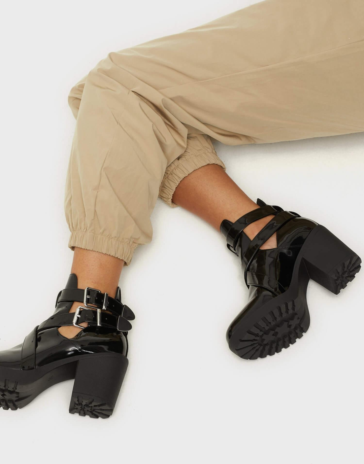 Svarta stövletter i lackfinish med mycket detaljer från NLY Shoes.