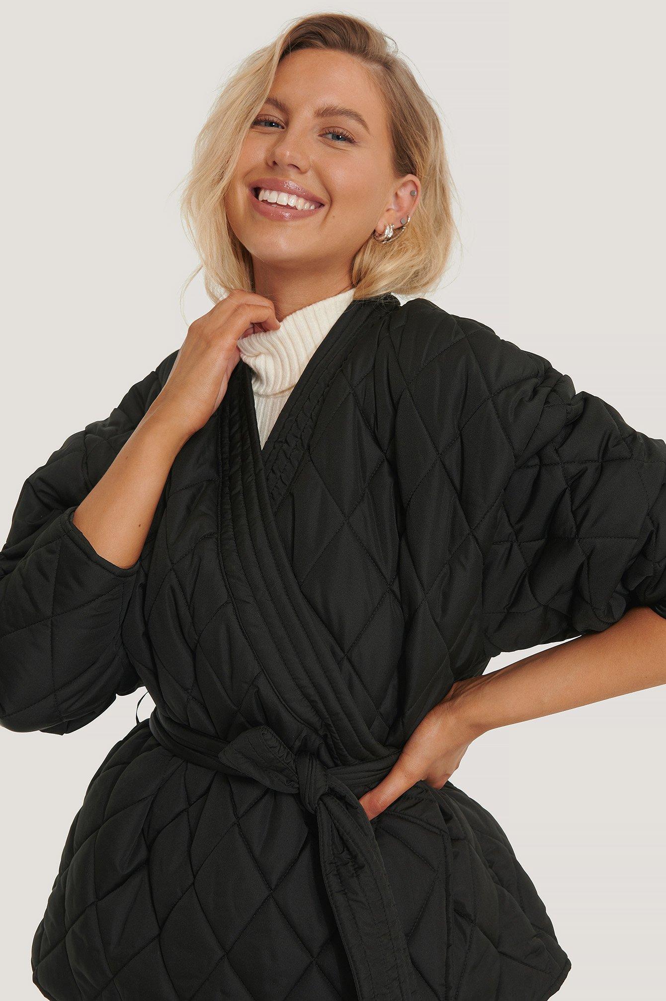 En svart kimonojacka i quiltat material från NA-KD.