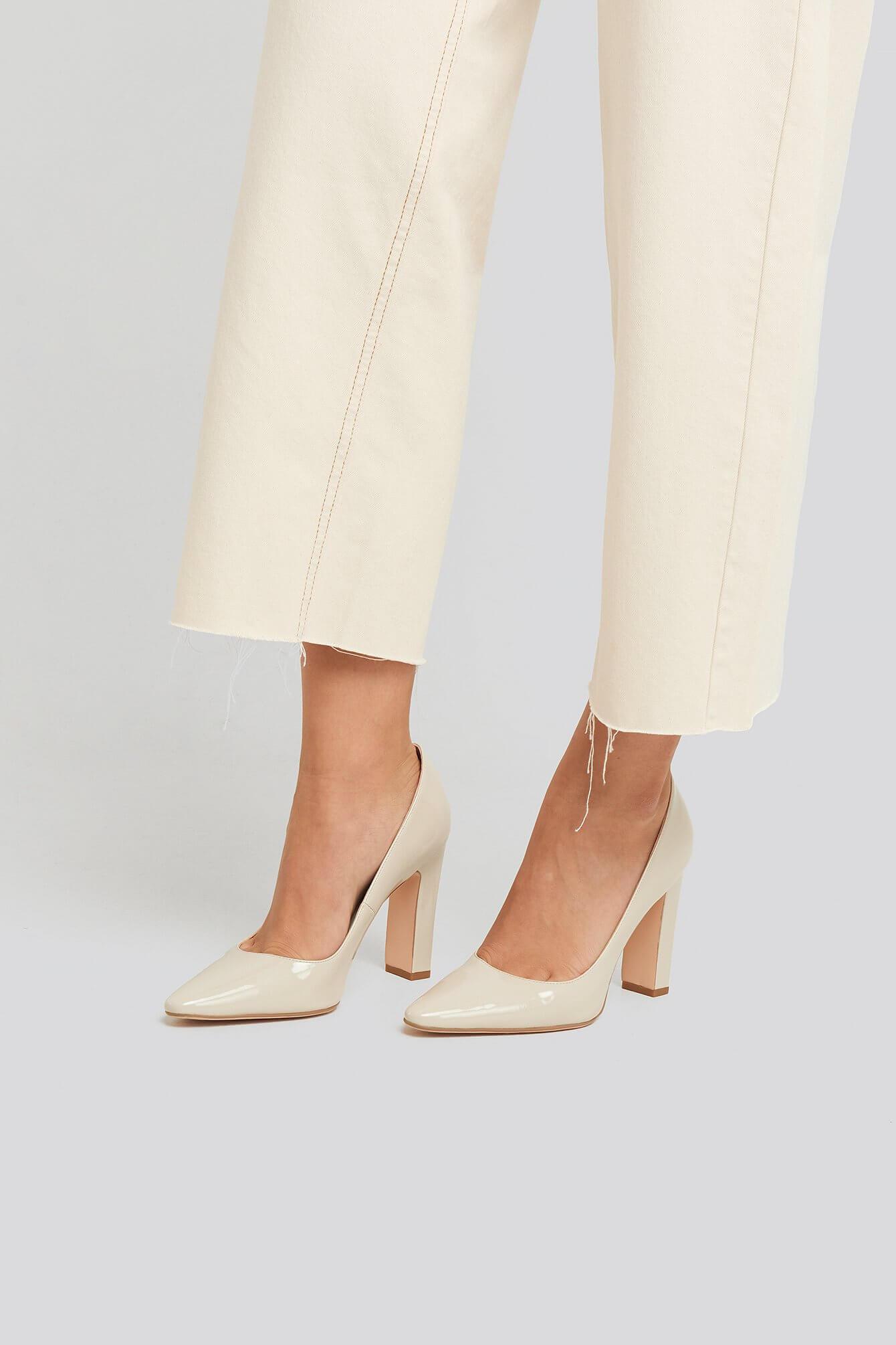 Vita pumps i lackat material från NA-KD Shoes.