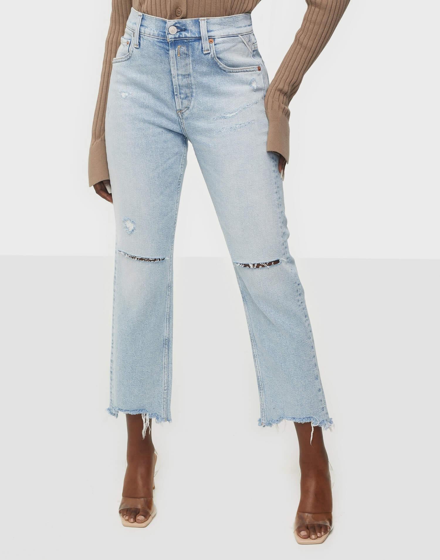Ett par blåa, lösa jeans med slitningar i knäna från Replay.