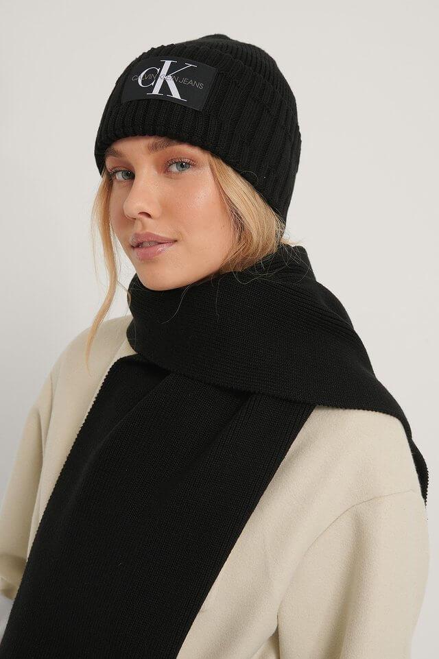 Ett set med en svart stickad scarf och mössa med logotyp från Calvin Klein Jeans.