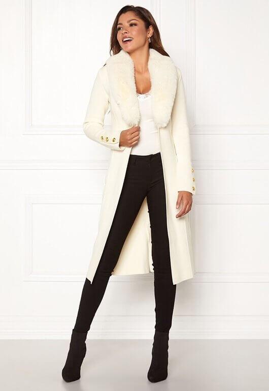 En vit, stickad kappa med fuskpälskrage från Chiara Forthi.