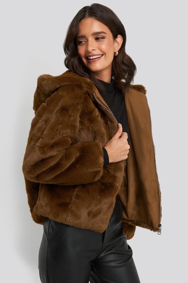 En brun fuskpälsjacka med huva från NA-KD.