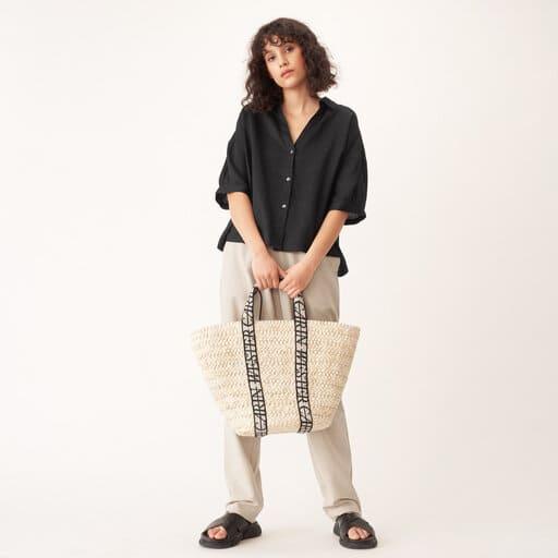 Rymlig stråväska från Carin Wester med breda, Carin Wester-prydda handtag i topp.