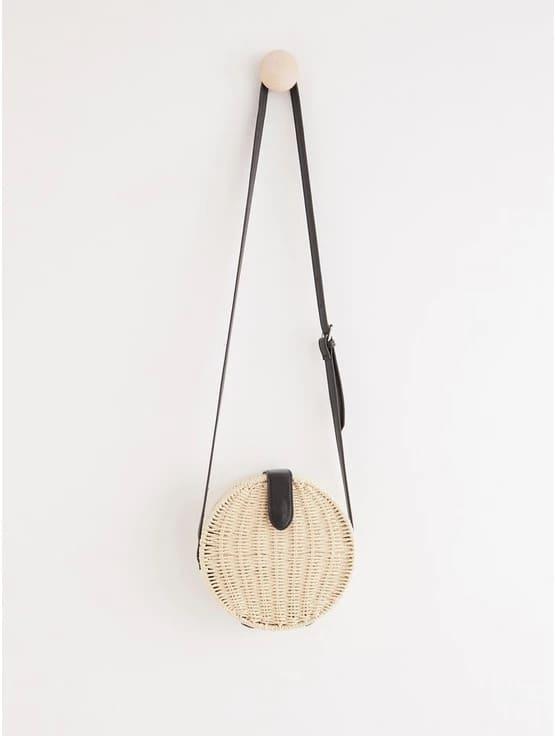 Liten rund väska med svarta detaljer i läderimitation och justerbart band.