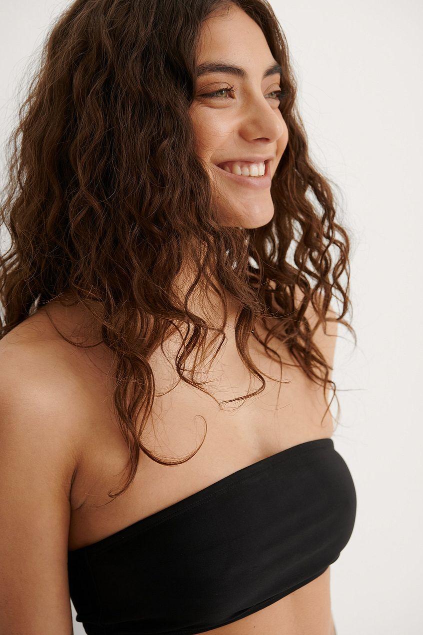 En svart bikinitopp i bandeau modell 2021