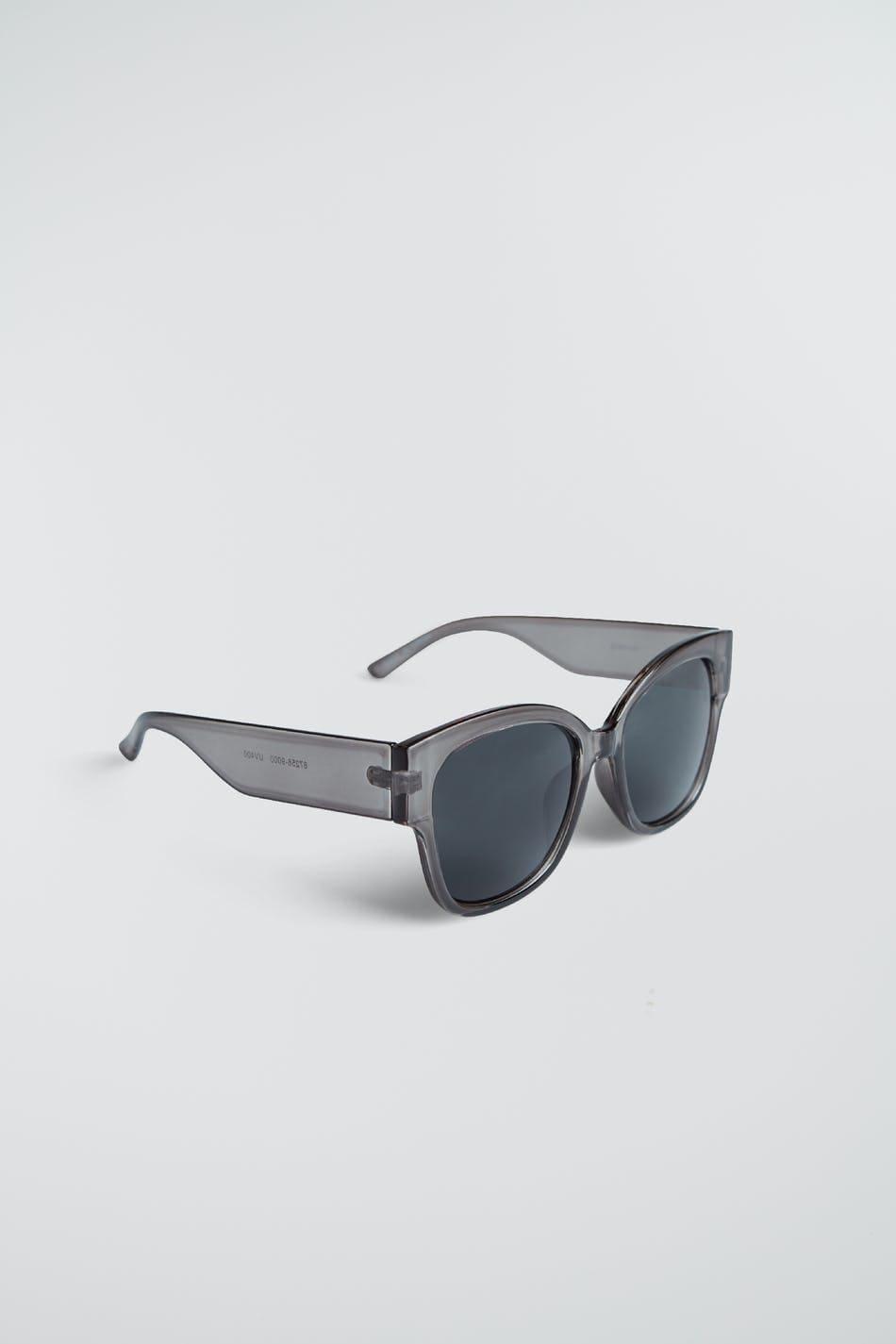 Stora solglasögon med en genomskinlig plastbåge. Solglasögonen är svarta.