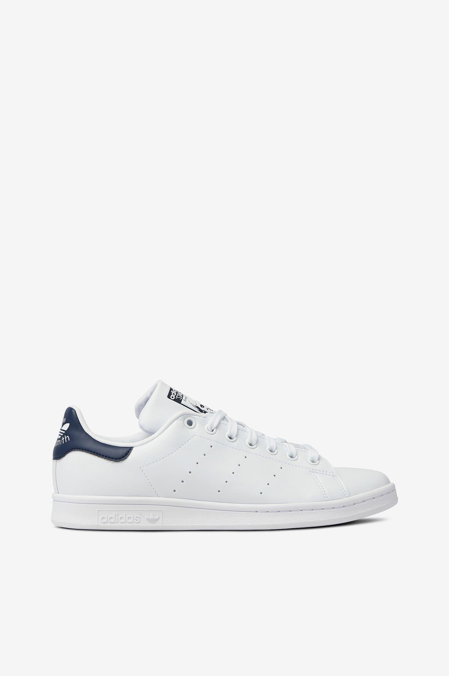 Ett par vita, veganska sneakers med mörkblå detalj från Adidas Originals i modellen Stan Smith.