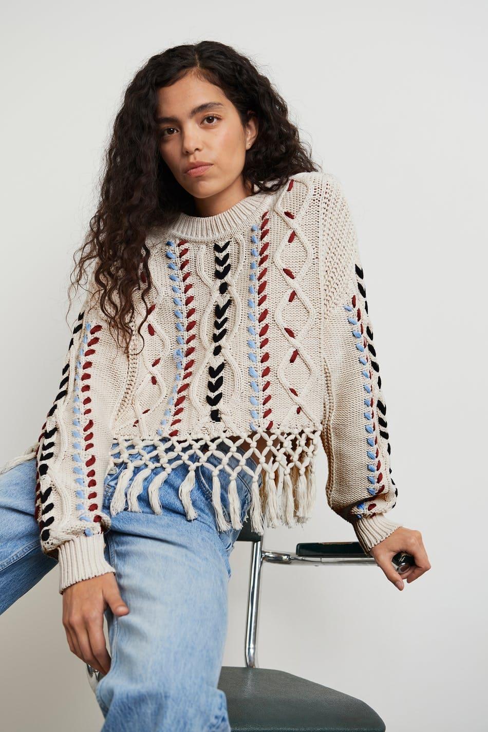 Stickad tröja med fina detaljer i färg och fransar nertill