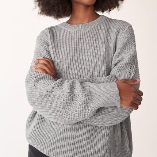 Grå stickad tröja med långa volymösa ärmar och fina stickningsdetaljer