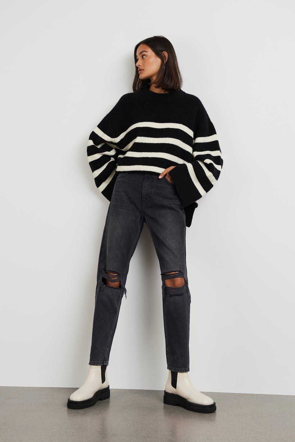 Mom jeans i svart med slitningar och korta ben