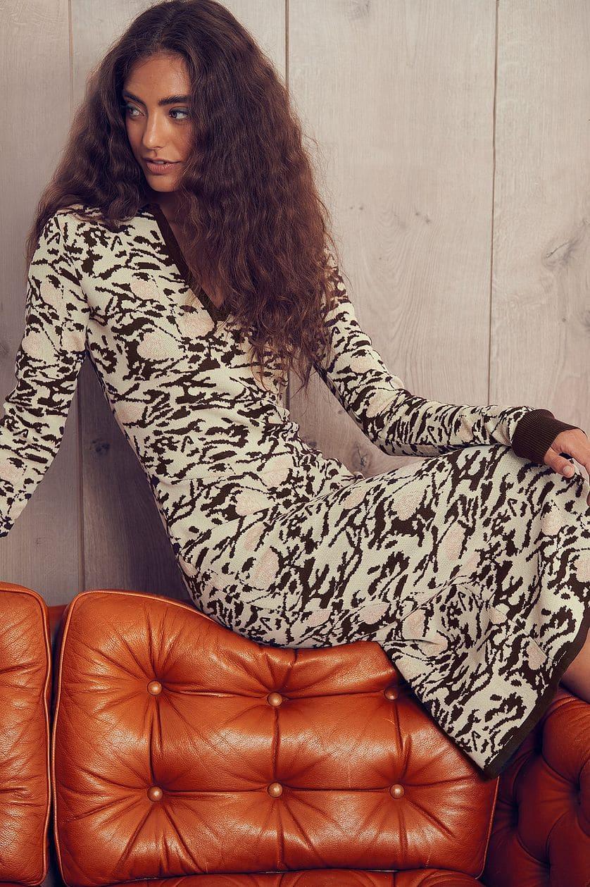 Stickad klänning med öppen krage och långa ärmar